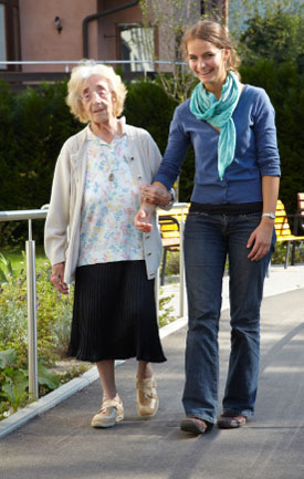 elderly person walking with assistance of companion